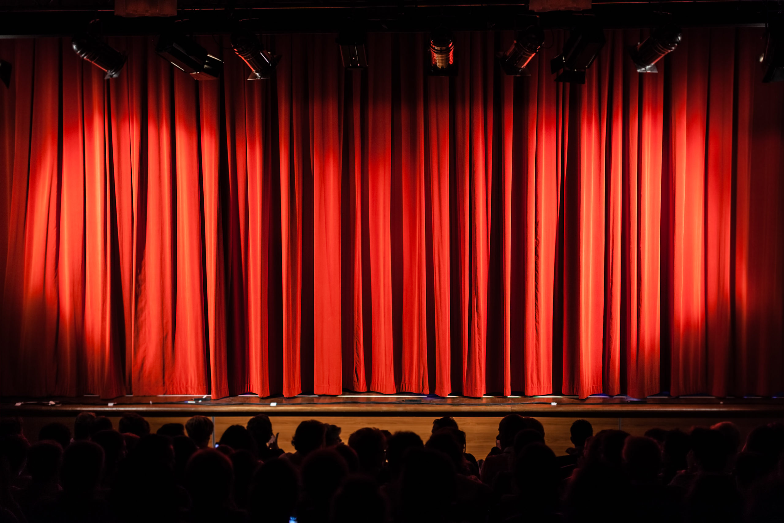 a closed red stage curtain in a small theater